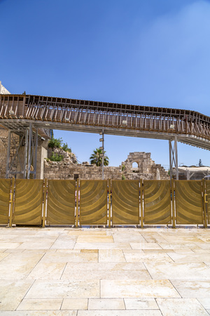 View of the separating wall in the Western Wall area. The brass blockades separate the women and men sections in the holy place. Above it, the gallery to the Dome of the Rock.