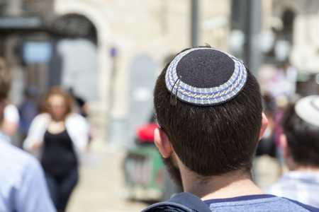 Jerusalem, Israel - June 14, 2018: Jewish man walking in the ancient streets of the old city of Jerusalem wearing a kippah or yarmulke, a traditional Jewish headwear.
