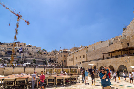 Jerusalem, Israel - June 14, 2018: People visiting and reading Torah around the Western Wall, the second holiest place to the Jews. The Wall is the last remnant of the second temple of Jews in Jerusalem.