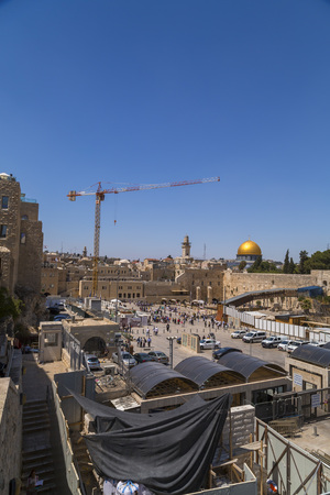 Jerusalem, Israel - June 14, 2018: View from the Temple Mount with the golden Dome of the Rock and people visiting the Western Wall downstairs, the holy site of the Old City in Jerusalem, Israel.