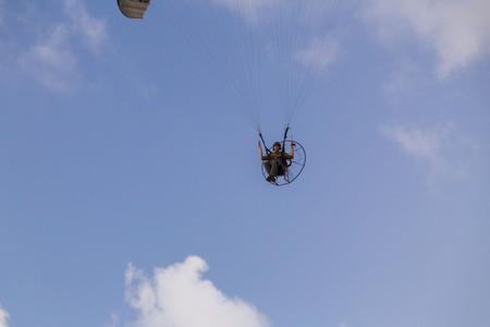 Haifa, Israel - June 18, 2018: Unidetified man flying with a paramotor, motor-powered paragliding parachute in the sky in Haifa, Israel. Фото со стока - 109864216
