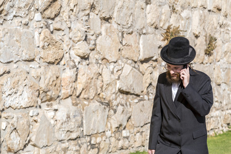 Jerusalem, Israel - June 14, 2018: An ultra-orthodox jewish or Haridi man in traditional religious outfit walking in the old city of Jerusalem. Editorial