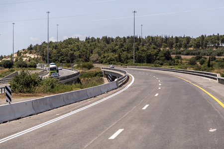 Highway with signs and vehicles in traffic from Jerusalem to Haifa on a sunny summer day.