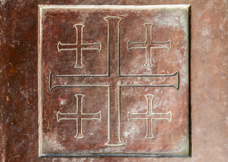 Close up texture of ancient metallic plate with cross sign engraved in a square frame