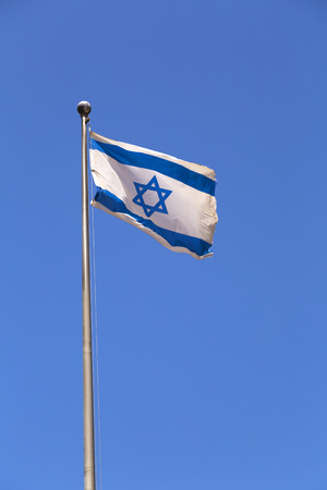Flag of Israel waving against the blue sky, blue Magen David sign and two stripes on white