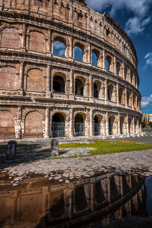 The Roman Colloseum or Flavian Amphitheather reflecting on rain water on the ground in Rome, Italy. Reklamní fotografie