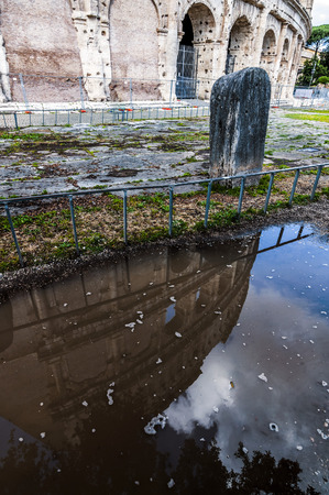 The Roman Colloseum or Flavian Amphitheather reflecting on rain water on the ground in Rome, Italy. Stockfoto - 122898772