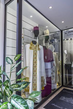 Rome, Italy - April 7, 2019: Display window of a clothing store selling religious Christian costumes near Vatican City, Rome. Publikacyjne