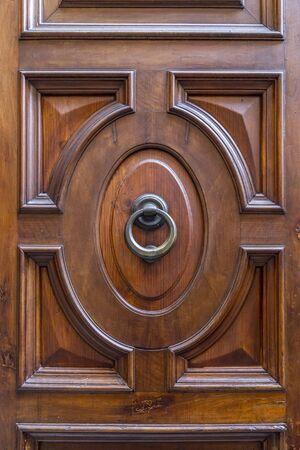 Close up shot of ancient metallic door knocker on wooden door found in Rome