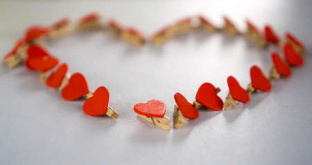 dozens: Love heart-shaped pattern composed of dozens of red heart shaped clip. Stock Photo