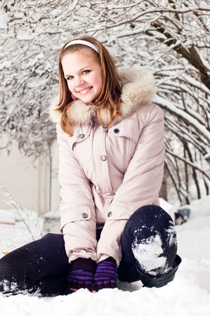 Beautiful young girl sits on to snow in warm clothes in winter outdoors photo