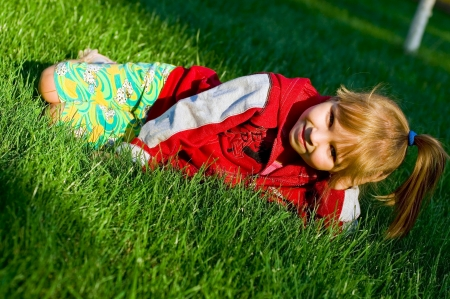 The small beautiful girl sits on a green lawn and laughs photo