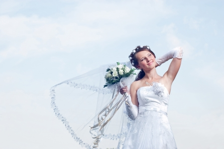 Wonderful and romantic bride on a background blue sky photo