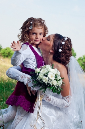 Wonderful young bride and beautiful little girl outdoors photo