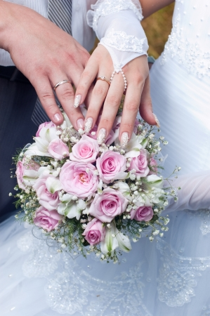 Wedding bouquet from tender roses, hands and rings photo