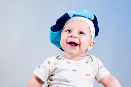 Amusing baby boy in a beret in a studio on a dark blue background photo