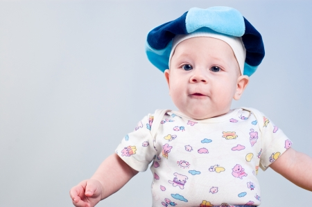 Amusing baby boy in a beret in a studio on a dark blue background Stock Photo - 13784171