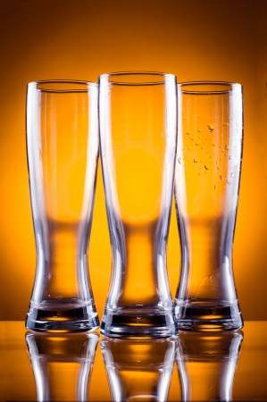 Three empty glass glasses for beer or drinks on a yellow background photo