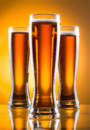 Three glass of beer over yellow background photo
