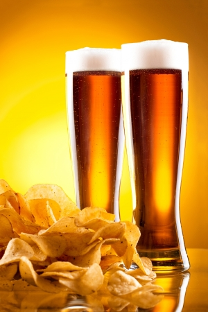 unhealthy snack: Two glass of beer and potato chips on a yellow background Stock Photo