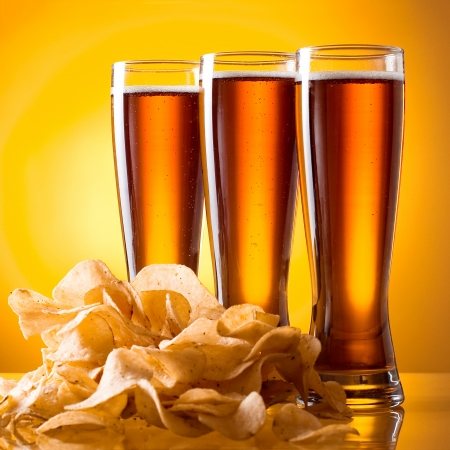 Three glass of beer and potato chips on a yellow background photo