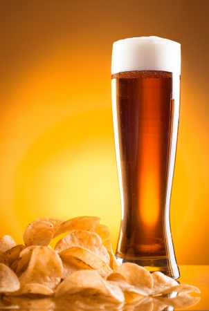 Single glass of beer and potato chips on a yellow background photo