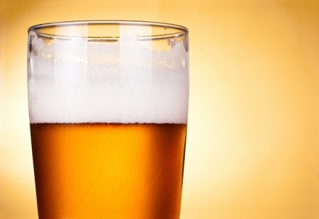 Glass of beer with froth close up photo