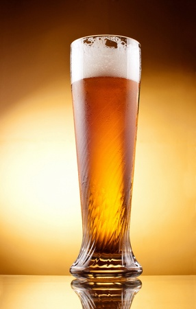 Frosty glass of light beer with froth over yellow background photo
