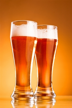 Two glass of beer over yellow background photo