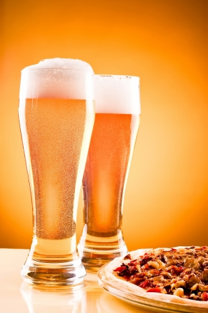 Two glass of beer and pizza over yellow background Stock Photo
