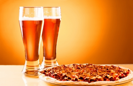 Two glass of beer and pizza over yellow background photo