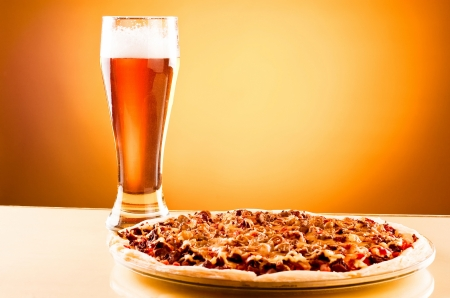 single beer: Single glass of beer and pizza over yellow background
