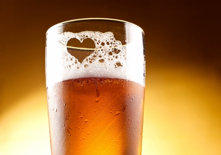 Glass of beer with the heart represented with froth close up over yellow background photo