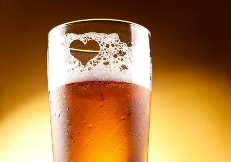 ámbar: Vaso de cerveza con el coraz�n representado con espuma de cerca sobre fondo amarillo Foto de archivo