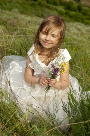 Beautiful girl in the clothes of bride on the field with the field flowers photo
