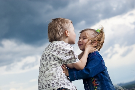 Little boy and girl is kissed on a background a landscape photo