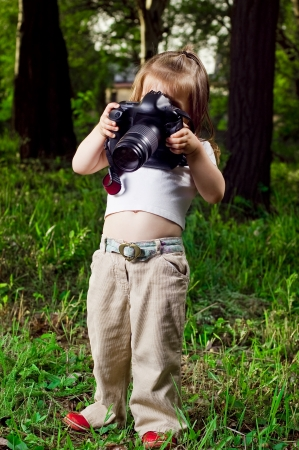 Amusing little girl takes pictures a professional camera photo