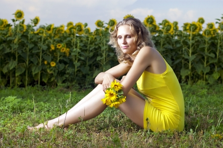 Beautiful girl in yellow clothes sits in the field with sunflowers photo