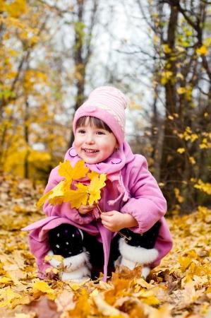 Cute child walking in autumn park photo
