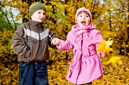 Little boy and girl play in a park in autumn photo