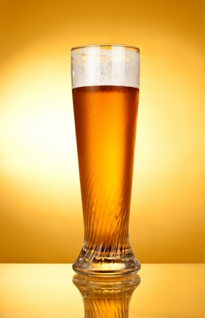 glass of beer on a yellow background photo