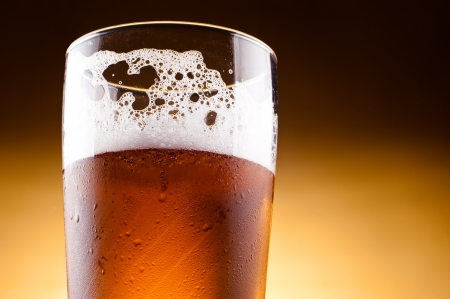 draught: Glass of beer with froth close up on a yellow background