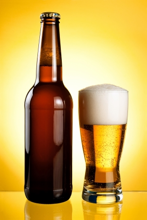 One glass and Bottle of fresh light beer on yellow background photo