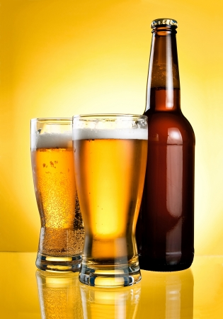 Two glasses and Bottle of fresh light beer on yellow background photo