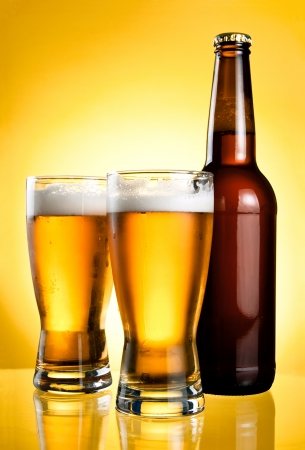 pilsner beer: Two glasses and Bottle of fresh light beer on yellow background Stock Photo