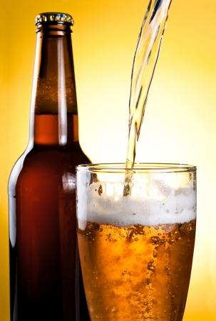 ビールはガラスと黄色の背景に瓶に注がれています。