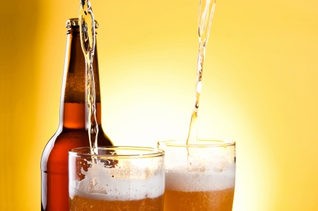 Beer Being Poured in Two glasses and Bottle on yellow background photo