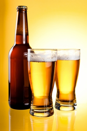 Two glasses and Bottle of fresh light beer on yellow background Stock Photo - 13855568