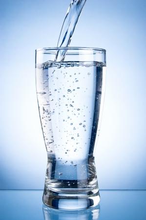 vaso con agua: Verter el agua en Glasson sobre un fondo azul Foto de archivo