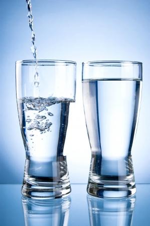 vasos de agua: Verter el agua en Glasson y vaso de agua sobre un fondo azul